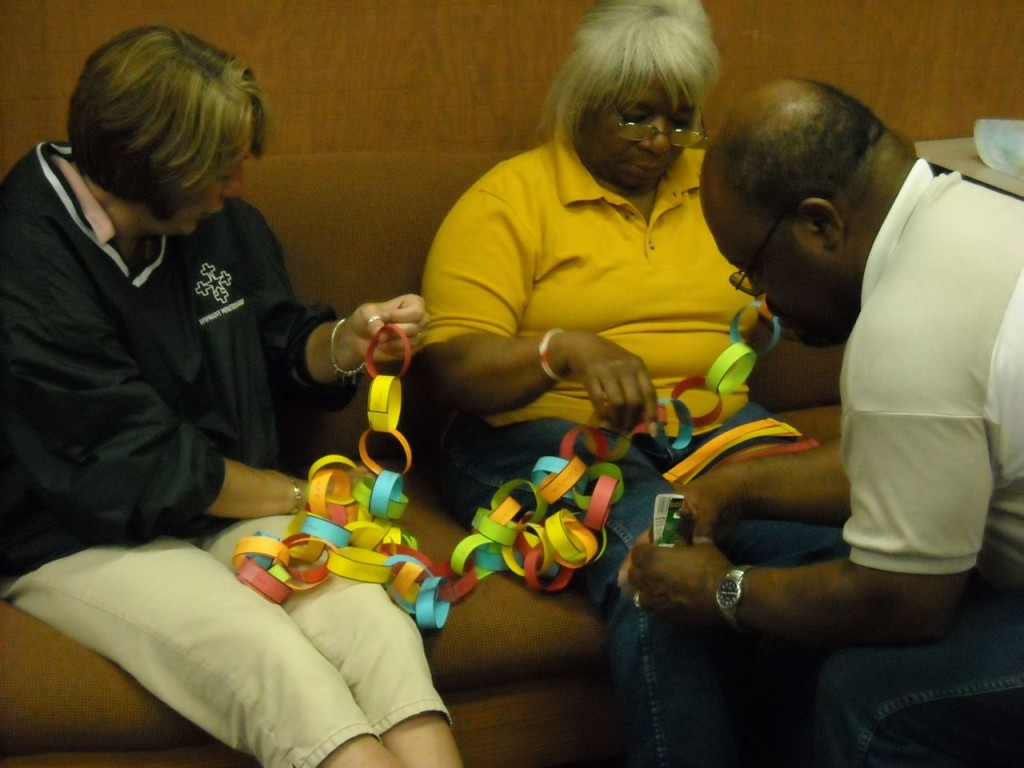 three team members work on assembling some 1,400 links in the prayer chain.