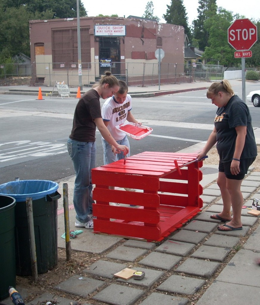 emmah, mitch and kaitlyn work on a recycling bin in front of harambee